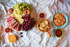 Snack time for anyone! maybe except vegans!. Layout of deli; meat rolls, cheese and fruits - grapes, oranges, blood oranges, plums on a white rustic plate on a stock image