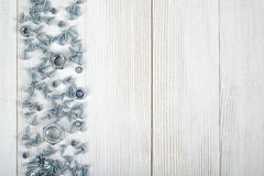 Layout with nuts and screws distributed on right side of wooden DIY workbench Stock Photos