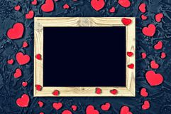 Valentine`s Day. Layout for the postcard. Wooden frame blank and hearts on a black stone background. Layout for the postcard. Wooden frame blank and hearts on a Royalty Free Stock Photo