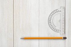 Layout with protractor and pencil on wooden surface. Royalty Free Stock Image