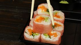 Layout of rolls to send to the consumer. Close up. People by sushi sticks puts the rolls on the dishes, rolls with various fillings are cooked for catering, chef stock video footage