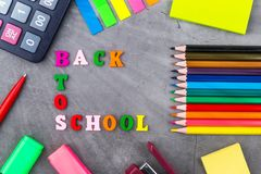The layout of school supplies on a dark gray background. Top view, the sun`s rays from the side. Flat lay. Back to school. The layout of school supplies on a royalty free stock images
