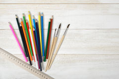 Layout of set colorful sharp pencils, centimeter rule and paint brushes on wooden blank board Royalty Free Stock Images