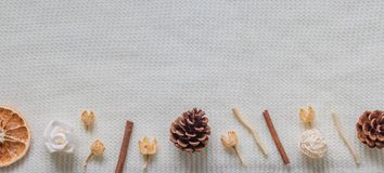 Layout from a white textured, woolen scarf or blanket. Spices, dried flowers, citrus, pine cone. Autumn and fertility. Layout from the perspective of the top stock photography