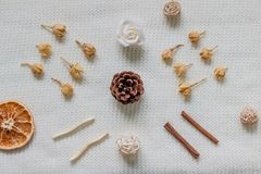Layout from a white textured, woolen scarf or blanket. Spices, dried flowers, citrus, pine cone. Autumn and fertility. Layout from the perspective of the top stock images