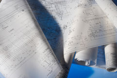 Layouts. Many different rolled-up engineering drawings on desk with blue background Stock Images
