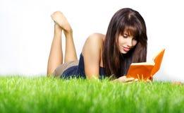 lays för bokgräsgreen läser kvinnan arkivfoto