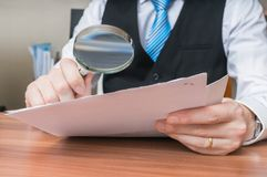 Laywer is analysing document with magnifying glass.  Stock Photos