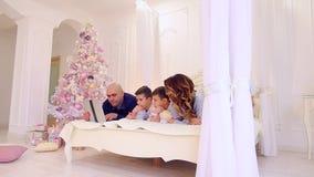 Lazer comum da grande e família amigável com o dispositivo na cama no quarto brilhante com árvore e decorações de Natal video estoque