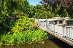 Lazienki Park in Warsaw. Poland, bridge on canal and vibrant foliage with flowers and reeds stock photos