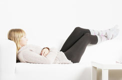 Laziness. Young blonde lazy woman laying down on white sofa royalty free stock photography