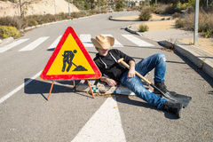 Laziness. Lazy guy on a road works site, a concept stock photo