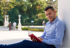 Laziness. Picture of a handsome man reading an interesting book Stock Image