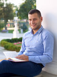 Laziness. Picture of a handsome man reading an interesting book Stock Photo