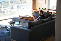 时髦人士lazing在一栋豪华公寓的长沙发 图库摄影