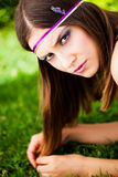 Lazing in the grass. Pretty brunette model lazing in the park wearing a purple and gold headband with lavender in her hair and a slight frown Royalty Free Stock Photos
