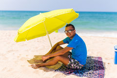 Lazing man in sun  under solar umbrella on towel enjoy the lazy time on the beach Stock Images