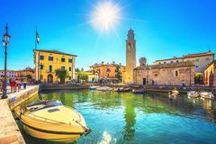 LAZISE, VENETO / ITALY - SEPTEMBER 28, 2018: Boats in old town port of Lazise and tourists walking royalty free stock photos