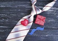 Lazo, corazón, bigote de papel, caja de regalo romántica de los presentes de la idea en un viejo fondo de madera negro Foto de archivo