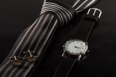Lazo de seda, mancuernas, reloj en un fondo negro Foto de archivo