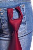 Lazo rojo en pantalones vaqueros de una hembra del bolsillo Foto de archivo libre de regalías