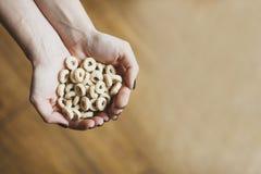 Lazos dulces del cereal en manos Avenas para el desayuno imagenes de archivo
