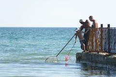 Lazurne,乌克兰, 26 05 2018年捉住虾的男孩和两个人在从老码头的黑海由箍网 库存图片