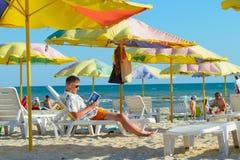 LAZURNE, KHERSON region, UKRAINA: Lipiec 05: Mężczyzna czyta książkę na plaży Zdjęcie Royalty Free