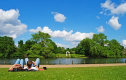 Lazy afternoon in Kensington Gardens. London, Great Britain - May 14, 2014. Grass lawn in Kensington Gardens with a couple lying on the grass, and six-metre Stock Image