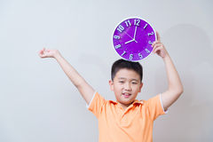 Lazy asian boy showing and holding purple or violet clock in stu Stock Photos