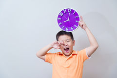 Lazy asian boy showing and holding purple or violet clock in stu Stock Photo