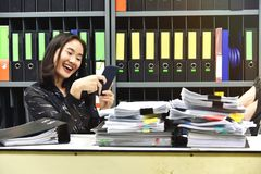 Lazy asian office woman using mobile smart phone in working time. royalty free stock photos
