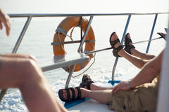 Lazy boat trip with sandals on railing Stock Photo