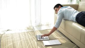 Lazy businessman. Cinemagraph of Vietnamese young businessman man typing on laptop when lying on the sofa stock video