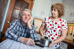 Lazy Caucasian man listens indifferently his wife, sitting with a TV remote in the kitchen Royalty Free Stock Photography