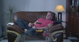 Lazy caucasian man lying on sofa in front of TV and sleeping. Adult redhead guy resting with chips and empty beer bottle