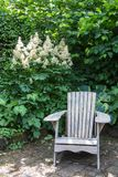 Lazy chair ouside. Lazy armchair in the garden in front of a blooming goats beard royalty free stock photos
