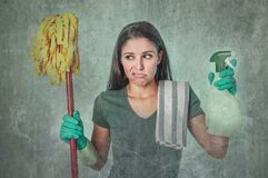 Lazy cleaning woman housewife or house maid service cleaner girl looking tired and frustrated holding mop and detergent spray. Grunge edit portrait of sad and Royalty Free Stock Photo