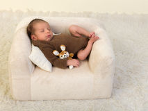 Lazy cute baby on couch Stock Image