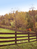 Lazy Day. Another perfect lazy, rural setting with a fence and a pasture surrounded by changing trees on a hilly landscape stock image
