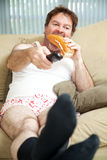 Lazy Day at Home. Unemployed man sitting on the couch in his underwear, watching TV and eating a sandwich royalty free stock photo