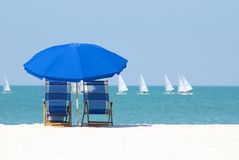 Lazy days. Beach chairs and umbrella to enjoy the passing sailboats Royalty Free Stock Photography