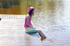 Lazy days on the bridge. Girl sitting on the bridge with her legs in the water Stock Photography