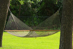 Lazy days hammock. Lazy relaxing days of summer. A  hammock with green grass between two trees Royalty Free Stock Photo