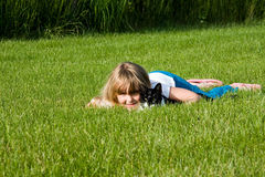 Lazy Days with pets. A little girl and her cat laying in the grass on a summer day Stock Image