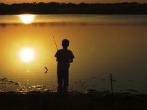 Lazy days of summer. Photo of little boy fishing at dusk royalty free stock images