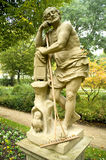 Lazy Diogenes. Diogenes sculpture in a relaxed position in a parc with a rake leaning unused in his arms stock images