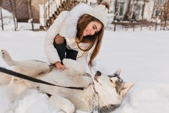 Lazy dog lying on the snow while beautiful girl in woolen hat sitting beside. Outdoor portrait of excited woman in white. Attire looking with love at her husky stock photos