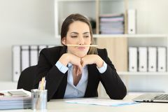 Lazy employee wasting time at office. Lazy employee wasting time playing with a pencil at office Stock Photos