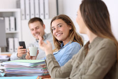 Lazy employees talking and wasting time at office Royalty Free Stock Photos